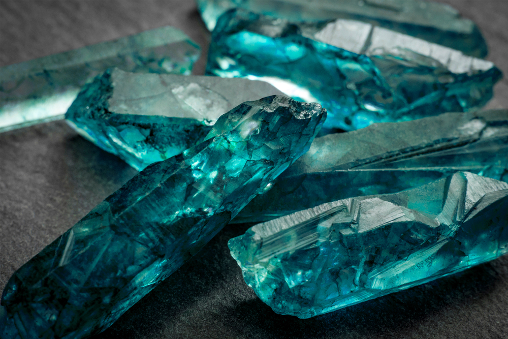 aquamarines-and-raw-crystal-gems-concept-with-closeup-of-a-bunch-of-blue-uncut-aquamarine-topaz-or-t-792228910